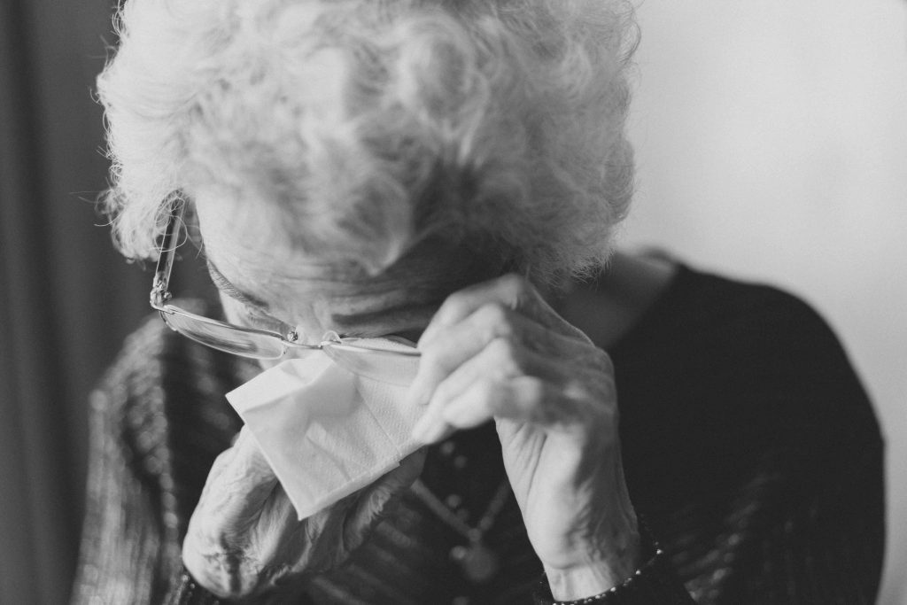 Photo of older woman wiping tears from her eyes. Photo by Jeremy Wong on Unsplash